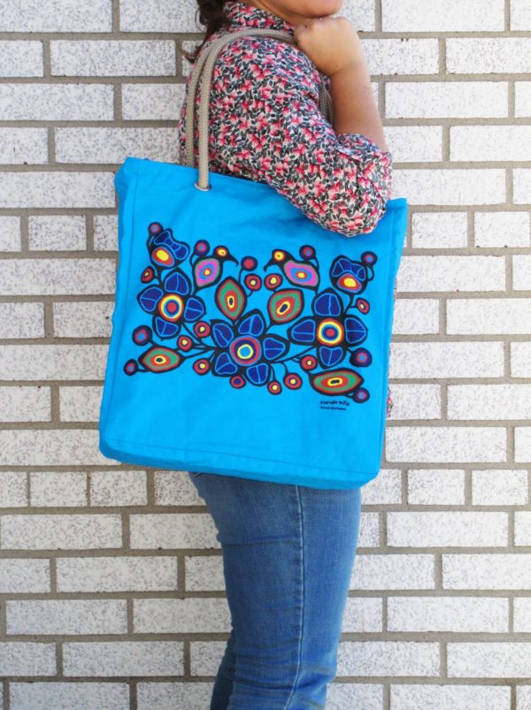 Blue bag with Flowers and Birds artwork, bag held by model