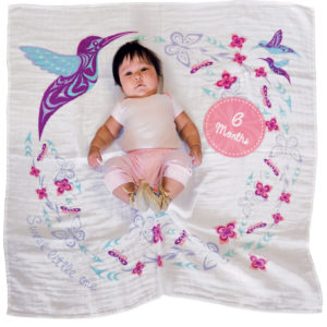 White, blue, purple, and pink Hummingbird Baby Blanket. Shows the 6 Month milestone card.